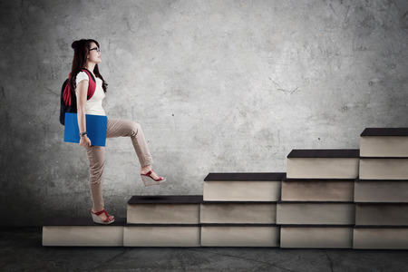 study: Image of a female college student walking upward on the books stair. Concept of study hard
