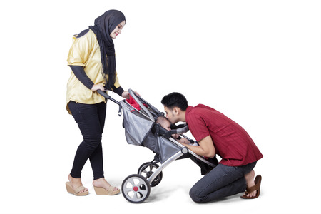 Portrait of young parents strolling and kissing their baby in the stroller, isolated on the background