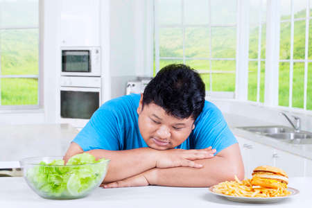 choose person: Confused person to choose food, looking at a bowl of salad and avoid junk food in the kitchen