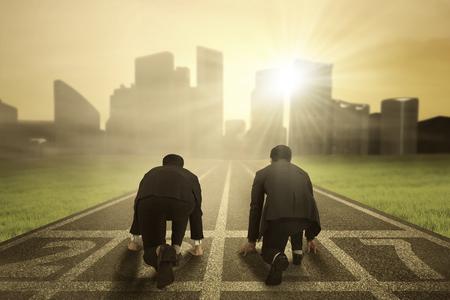 Achteraanzicht van twee zakenlieden klaar voor een wedstrijd en proberen hun succes met nummers 2017 op het spoor te achtervolgen Stockfoto