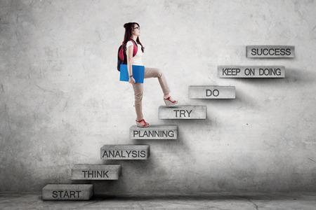 전략 계획에 들고 배낭 성공에 이르는 동안 계단에 걷는 여자 고등학교 학생의 이미지 스톡 콘텐츠