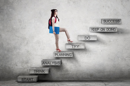Image of a female high school student walking on the stairs while carrying backpack with strategy plan leading to success Stock Photo