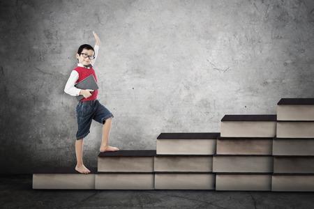 Afbeelding van een mannelijke basisschool student die zich op de boeken trap. Concept van hard studeren