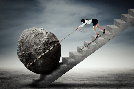 Image of a young businesswoman dragging a big stone while climbing up a stairway