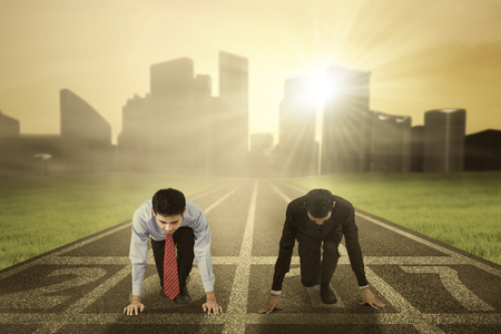 two visions: Image of two businessmen in ready to compete and try to chase their dream with numbers 2017 on the running track Stock Photo
