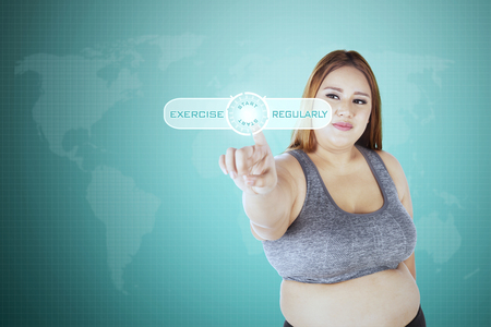 regularly: Portrait of obese woman touching virtual screen with exercise regularly text on the screen