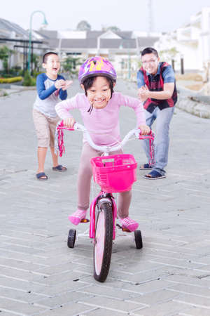 a young family: Image of little girl tries to ride a bicycle with her family giving support on the back Stock Photo
