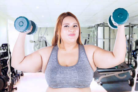 obeso: Portrait of obese woman lifting dumbbells while standing at the fitness center Foto de archivo