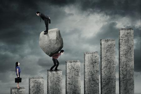 carga: El hombre de negocios de pie sobre una gran piedra y mirando a una mujer de negocios, mientras que su compañero de llevar a la piedra en el gráfico