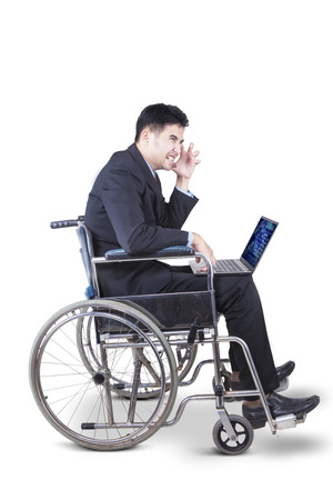 Image of handicapped businessman looks depressed with laptop and wheelchair in the studio