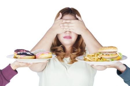 Portret van vette vrouw sluit haar ogen met behulp van handen en junk food, geïsoleerd afwijzen op een witte achtergrond