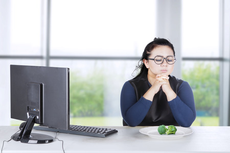 Young businesswoman prays with broccoli on plate while sitting in front of her computer Stock Photo