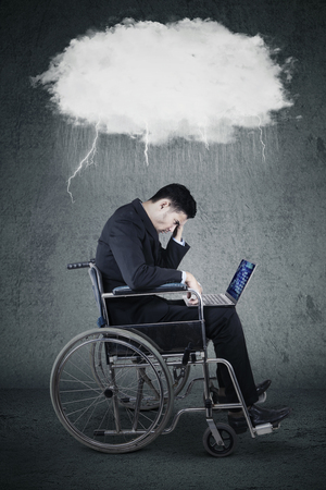 thundercloud: Portrait of stressful businessman sitting on wheelchair while using laptop with a thundercloud above his head Stock Photo