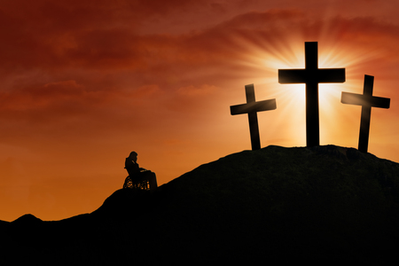 Silhouette of a stressful disabled male sitting on a wheelchair while repenting at the cross on the hill
