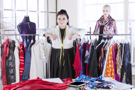 Professional designer standing in her workplace with material textile on the table Stock Photo