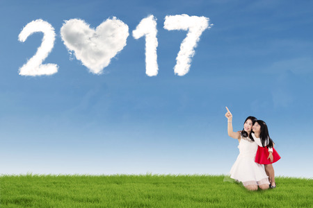 asian children: Young woman embracing her daughter on the meadow while pointing at clouds shaped a heart and numbers 2017