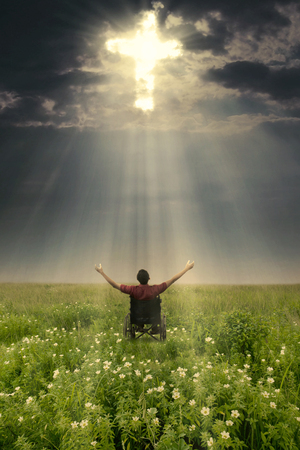 worshiper: Handicapped male raising hands and looking at the light cross on the sky while sitting in a wheelchair Stock Photo