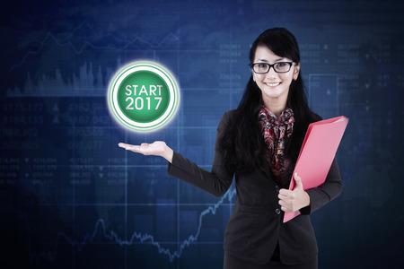 secretaria: Imagen de la hermosa mujer empresaria es la celebración de un documento mientras que muestra inicio de 2017, por el botón virtual Foto de archivo