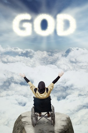 paraplegic: Image of disabled muslim woman sitting on a wheelchair while raising hand and looking at god text in the sky Stock Photo