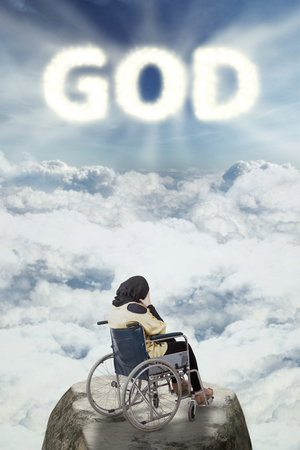 worshiper: Back view of a stressful disabled Muslim woman sitting on a wheelchair with god text in the sky