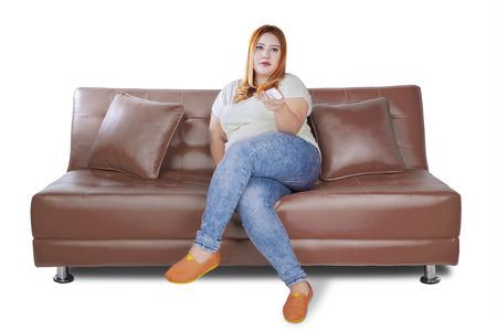mujer gorda: Mujer gorda en el sofá viendo la televisión mientras se mantiene el control remoto, aislado en fondo blanco