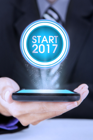 notebook computer: Close up of businessman holding smartphone while showing a virtual button to start 2017 Stock Photo