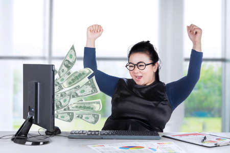 pay raise: Young female entrepreneur looking money out of her computer while raising her hands Stock Photo