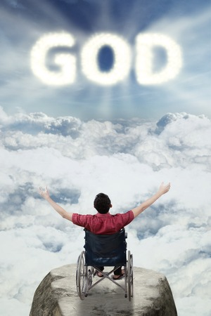 worshiper: Back view of handicapped man is sitting on a wheelchair and raising hands while looking at light god text in the sky Stock Photo