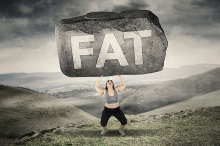 standing stone: Picture of obese woman lifting big stone with fat word while standing in hills Stock Photo
