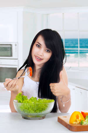 korean salad: Pretty young woman showing thumb up while eating a bowl of vegetable salad in the kitchen at home Stock Photo