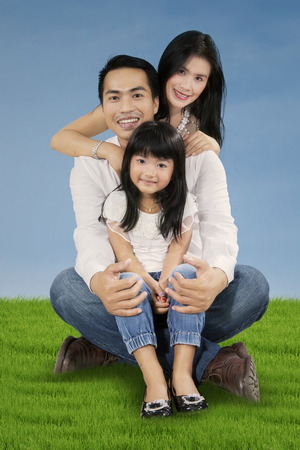 asian lifestyle: Portrait of happy Asian family smiling at the camera while sitting on the meadow at springtime