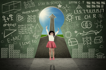 asia children: Portrait of a cheerful little girl jumps near a door shaped a keyhole with upward arrow and doodles on the blackboard Stock Photo
