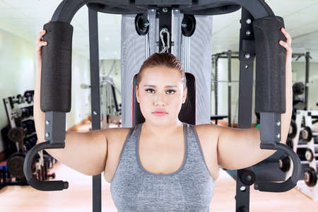 woman muscle: Portrait of overweight woman looking at the camera while exercising on a shoulder press machine in the fitness center