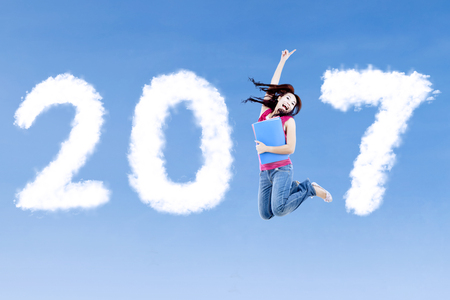 Concept of New Year 2017. Cheerful female college student jumping on the blue sky with clouds shaped number 2017 Stock Photo