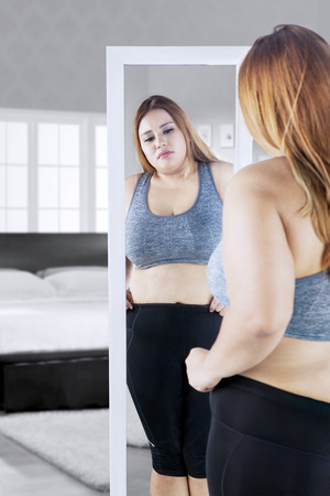 Image of overweight young woman looking at the mirror while touching her belly in the bedroom Stock Photo