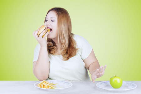 Portrait of overweight blonde woman rejecting a fresh apple fruit and choosing to eat hamburger Stock Photo