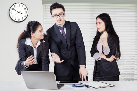 debating: Three young businesspeople standing in the office while discussing and debating with a laptop on desk