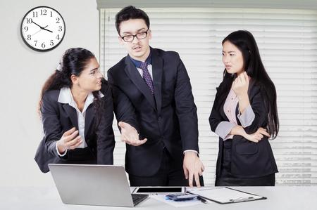 conflicto: Tres jóvenes empresarios de pie en la oficina mientras discutiendo y debatiendo con un ordenador portátil en el escritorio Foto de archivo