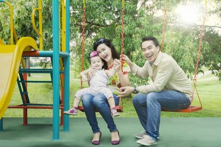 Portret van het vrolijke familie spelen samen in speelplaats terwijl het glimlachen bij de camera