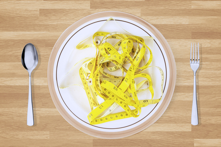 tapeline: Close up of yellow tape measure on a plate with cutlery on the wooden table