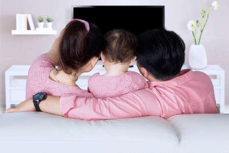 detras de: Vista trasera de la familia feliz viendo la televisión mientras está sentado en el sofá en la sala de estar