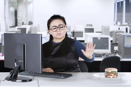 to restrain: Picture of an overweight beautiful woman refusing burger on the plate and working with a computer in the office