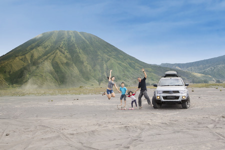 Joyful family jump on volcanic desert, shot outdoors Stock Photo