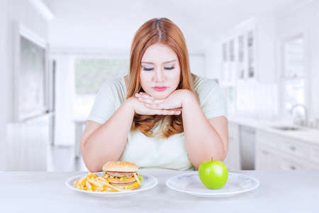 woman eating: Picture of blonde woman looks confused to choose a fresh apple fruit or hamburger, shot in the kitchen