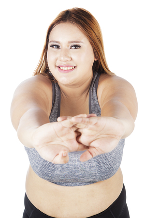 Image of obese female smiling at the camera while doing warm up by stretching her hands on the studio