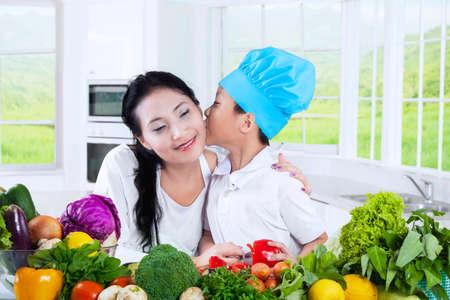 mama e hijo: Retrato de un niño pequeño que besa a su madre mientras cocina verduras en la cocina de su casa