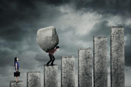 carga: Empresaria joven que mira a su compañero que lleva una gran roca mientras camina hacia arriba en el gráfico