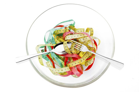 tapeline: Image of colourful measuring tape with cutlery on a glass bowl, isolated on white background Stock Photo