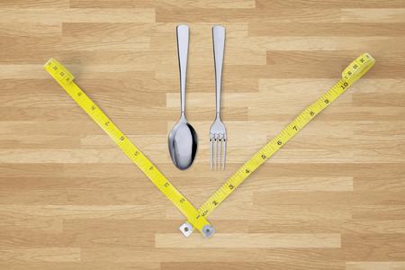 metro de medir: Imagen de dos metros de cinta de medir y cuchara de acero y el tenedor en la mesa de madera, concepto de la dieta