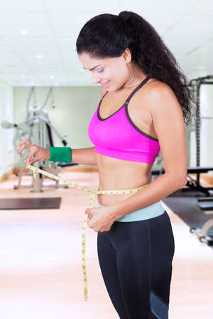 waistline: Image of a beautiful Indian woman is measuring her waistline with measure tape in the gym center Stock Photo